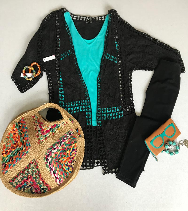 Woman's black blouse, purse, jewelry, and eye-case