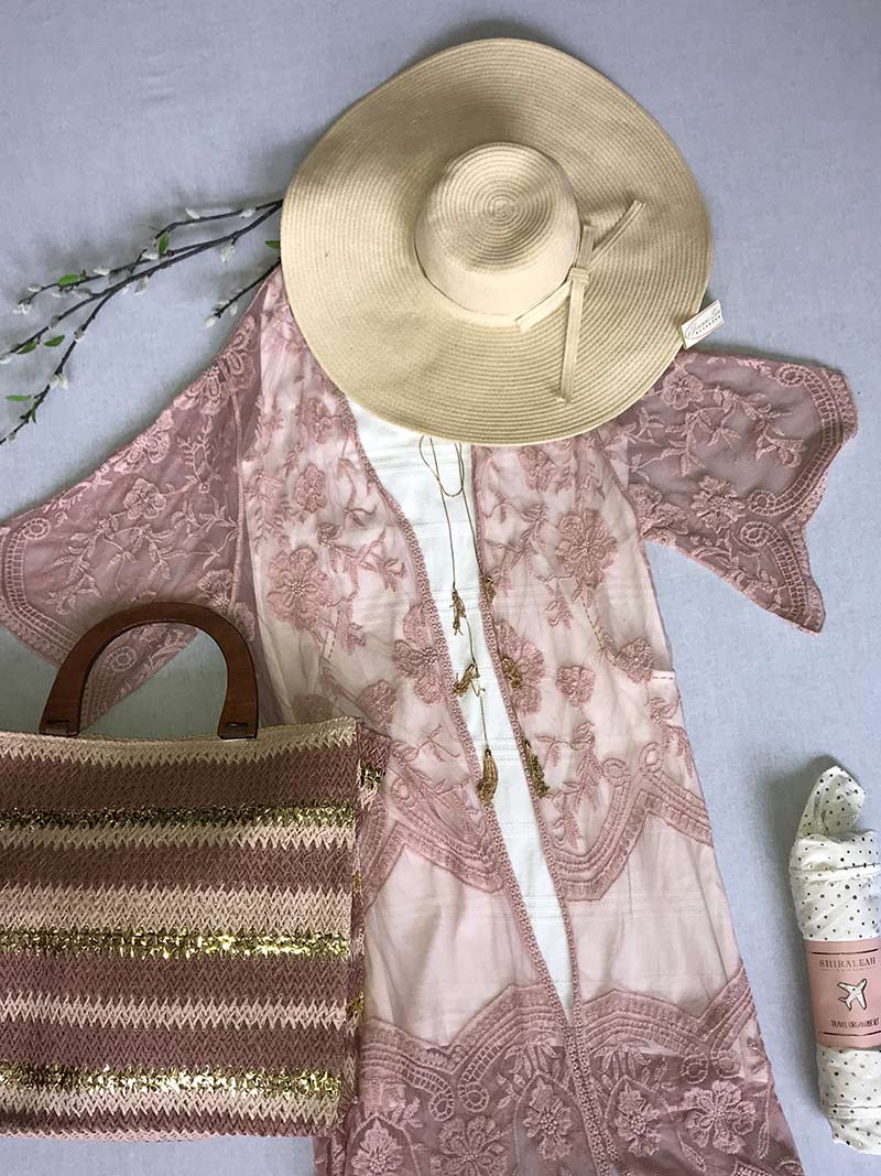 Woman's pink blouse, straw hat and straw bag