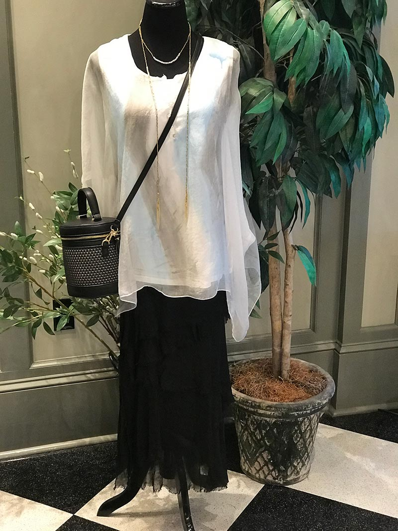 white blouse, black shirt, and black purse on display
